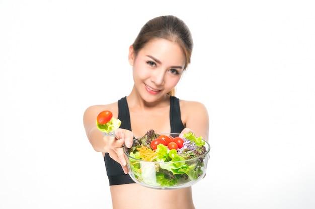 Garota em uma suíte de aptidão detém uma tigela de salada.