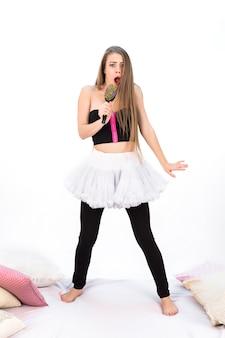 Garota emocional canta em uma escova de cabelo colorida, imitando um microfone, na cama