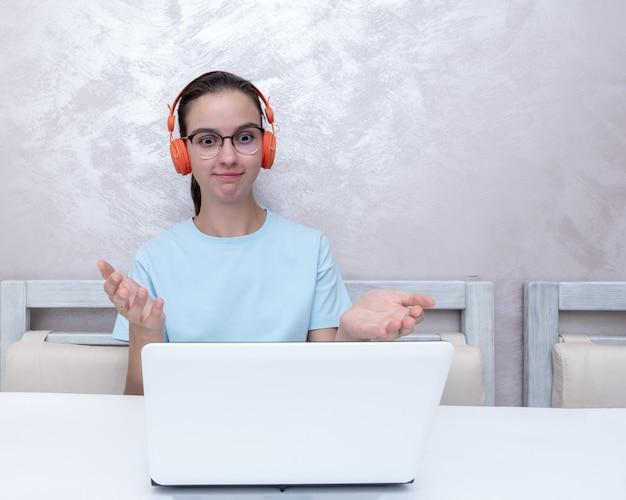 Garota emocional surpresa, assistindo a tutoriais em vídeo, comunicando-se com amigos em um laptop em casa.