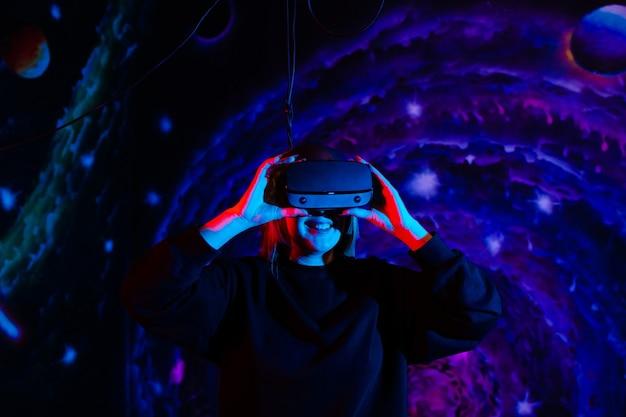 Garota emocionalmente feliz em óculos modernos de realidade virtual com luz neon vermelha e azul no fundo do espaço na sala de jogos