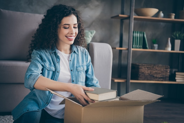 Garota empacotando suas próprias coisas, movendo-se em um loft moderno em estilo industrial, sala de estar interna
