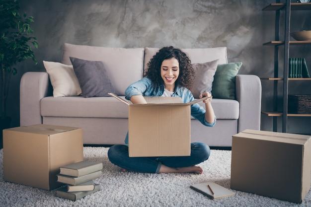 Garota empacotando suas próprias coisas preparando-se para mudar em um loft moderno em estilo industrial com sala de estar