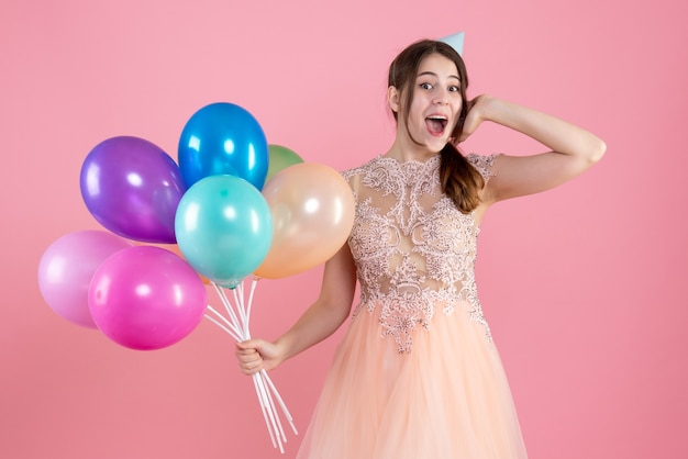 Garota empolgada de frente com boné de festa segurando balões