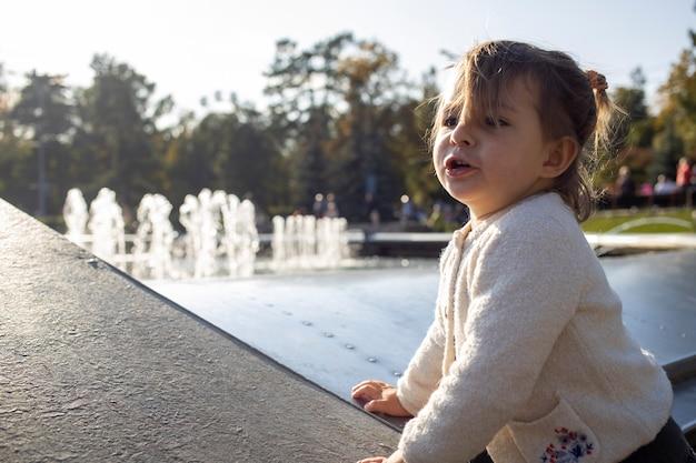 Garota encantadora da criança faz caretas e caretas no contexto do parque. a criança brinca alegremente. infância feliz