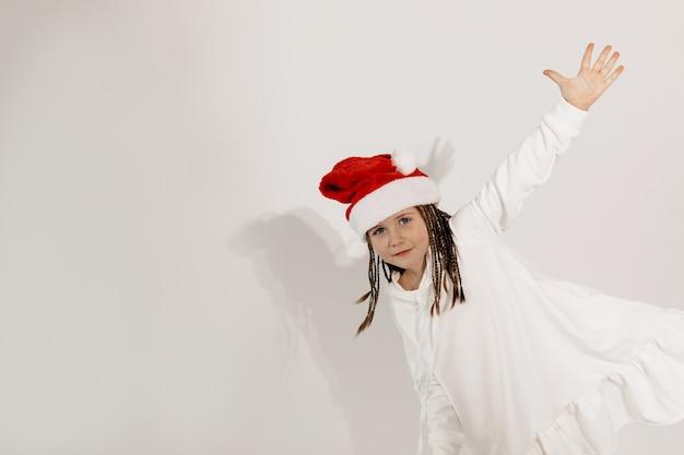 Garota encantadora engraçada com chapéu de papai noel se divertindo com clima de natal