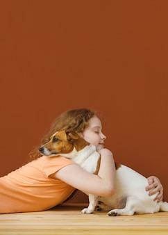 Garota encaracolada, abraçando o seu cão amigo.