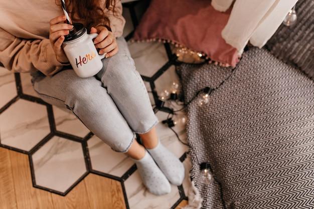 Garota encaracolada em jeans, sentada no chão e bebendo uma bebida quente. retrato aéreo interno do modelo feminino com uma xícara de chá.