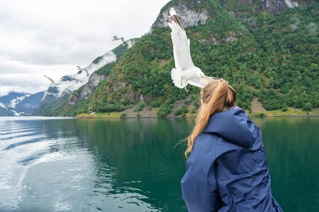 Garota encontrando uma grande gaivota em sognefjord