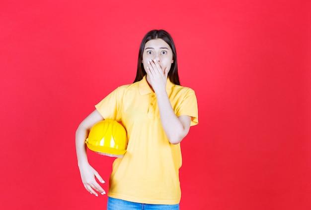 Garota engenheira com dresscode amarelo segurando um capacete de segurança amarelo e parece apavorada e assustada.