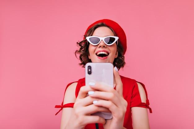 Garota engraçada caucasiana com roupa francesa, usando telefone para selfie. rindo senhora morena na boina vermelha, tirando foto de si mesma.