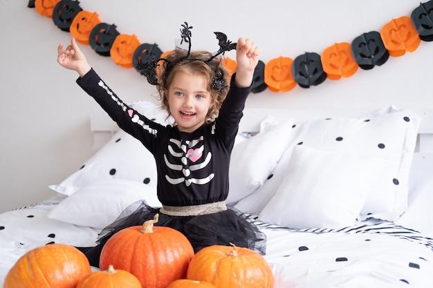 Garota engraçada caucasiana fantasiada de bruxa se divertindo em decoração para o quarto de halloween