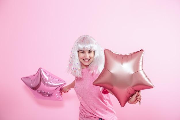Garota engraçada com cabelo prateado dá um sorriso e emoção em fundo rosa. jovem mulher ou adolescente com balões e confetes