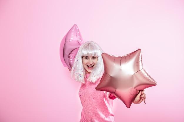 Garota engraçada com cabelo prateado dá um sorriso e emoção. jovem mulher ou adolescente com balões e confetes