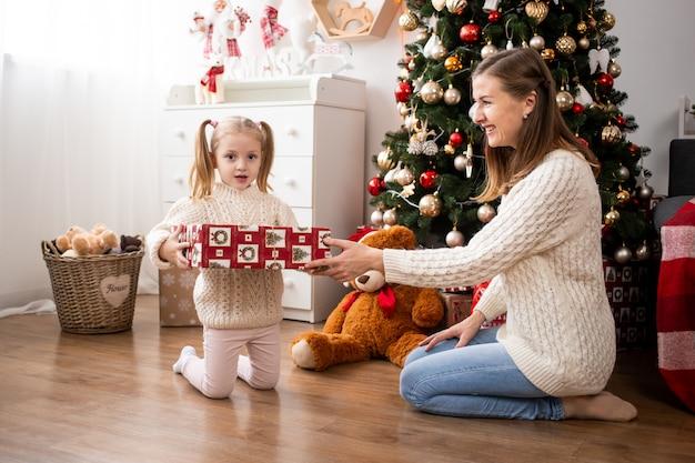 Garota engraçada com caixa de presente em casa perto de árvore de natal
