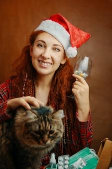 Garota engraçada com chapéu de papai noel segurar o copo de comprimidos e acariciar o gato fofo. mulher ruiva de pijama xadrez. natal em quarentena. ao lado dela está a caixa de comprimidos, máscaras médicas e anti-sépticos.