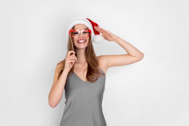 Garota engraçada com chapéu de papai noel usa óculos de coração de mentira, isolados no fundo branco, festa de ano novo