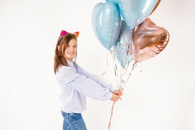 Garota engraçada com orelhas de gatos segurando balões. aniversário do conceito