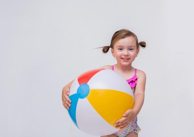 Garota engraçada com rabos de cavalo em um maiô e uma bola inflável em um branco isolado