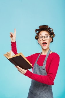 Garota engraçada com rolinhos e óculos lê e aponta