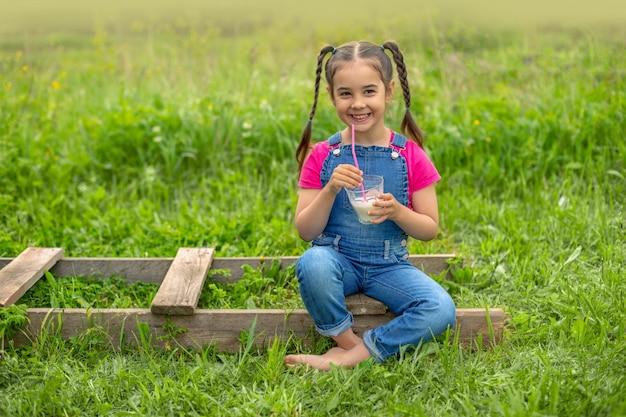 Garota engraçada de macacão jeans e uma camiseta rosa, segura um copo de leite em uma grama verde