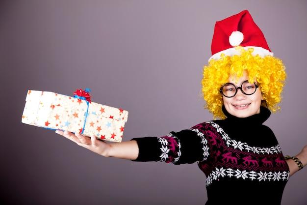 Garota engraçada de óculos com presentes de natal. tiro do estúdio.