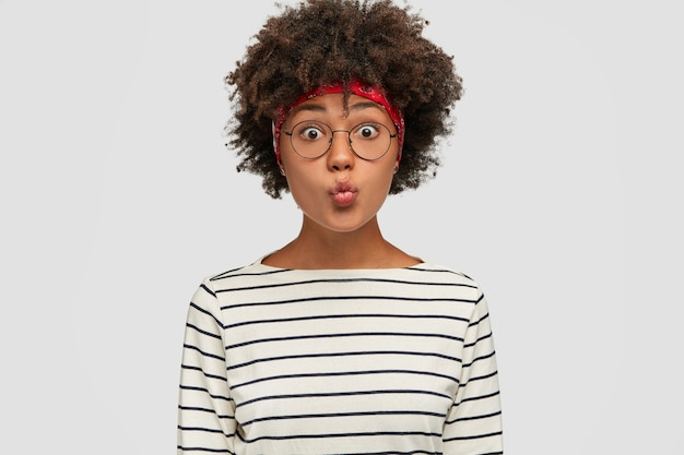 Garota engraçada de pele escura dobra os lábios para beijar, olha com os olhos arregalados, faz careta, usa uma jaqueta listrada preta e branca