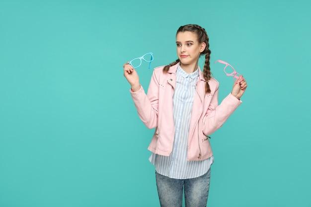 Garota engraçada duvidosa em estilo casual ou hipster, penteado pigtail, em pé, segurando óculos azuis e rosa e desviando o olhar com uma cara confusa, foto de estúdio interna, isolada em fundo azul ou verde