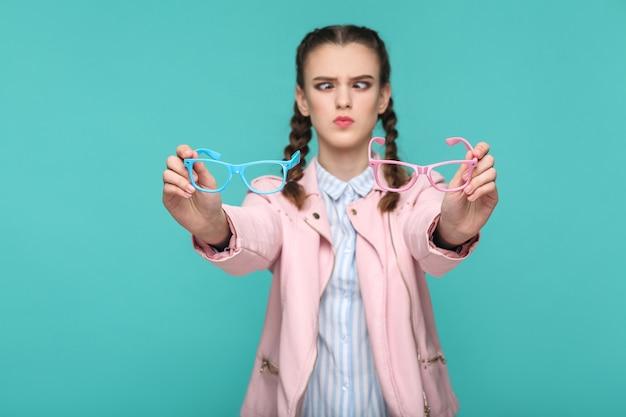 Garota engraçada duvidosa no estilo casual ou hipster, penteado pigtail, em pé, segurando óculos azuis e rosa e olhando para a câmera com o olho cruzado, foto de estúdio interna, isolada no fundo verde