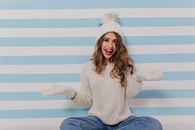 Garota engraçada e alegre em espanto estende as mãos. senhora com roupa quente, parecendo emocionalmente sentada no chão