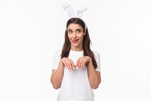 Garota engraçada e boba, brincalhona com orelhas de coelho, camiseta, olhando para longe e lambendo os lábios