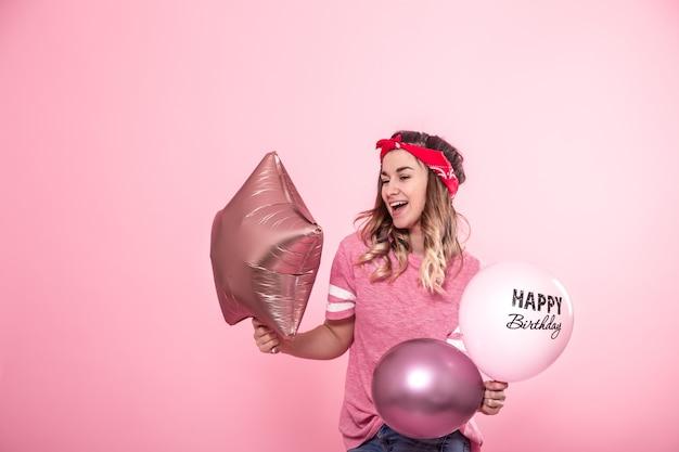 Garota engraçada em uma camiseta rosa com balões feliz aniversário dá um sorriso e emoções em uma parede rosa