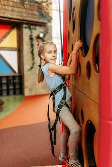 Garota engraçada escalando paredes em centro de jogos infantis