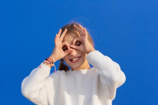 Garota engraçada fazendo óculos com as mãos, isoladas.
