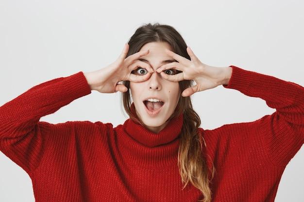 Garota engraçada fazer óculos de mão