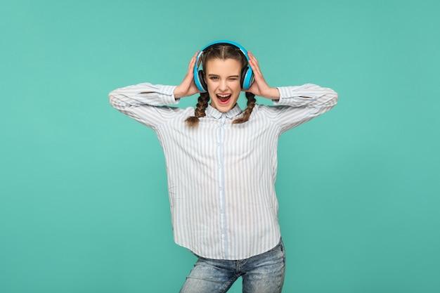 Garota engraçada feliz em camisa azul listrada e penteado pigtail, ouvindo música em pé com fone de ouvido, olhando para a câmera com rosto safisfied, estúdio interno, isolado em fundo azul ou verde