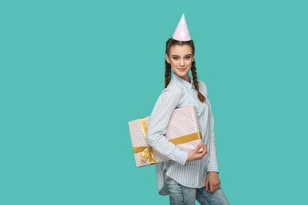 Garota engraçada feliz em uma camisa azul listrada em pé com uma caixa de presente pontilhada e um boné de aniversário na cabeça, olhando para a câmera com um rosto sorridente safisfied, estúdio interno, isolado no fundo verde