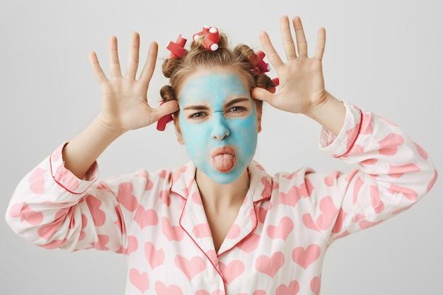 Garota engraçada infantil com bobes de cabelo e máscara facial mostrando a língua