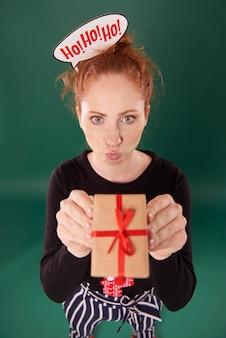 Garota engraçada mostrando um presente de natal