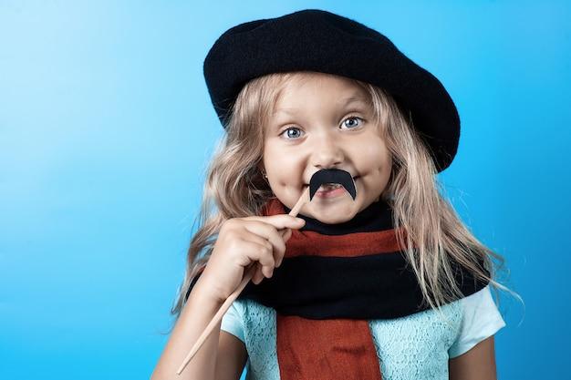 Garota engraçada na boina preta, cachecol e bigode no palito em azul