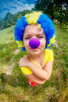 Garota engraçada na peruca de palhaço com nariz azul
