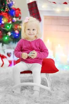 Garota engraçada na sala de estar e árvore de natal no fundo