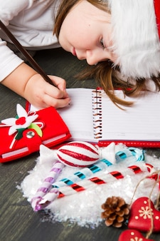 Garota engraçada no chapéu de papai noel escreve carta para o papai noel perto de natal de
