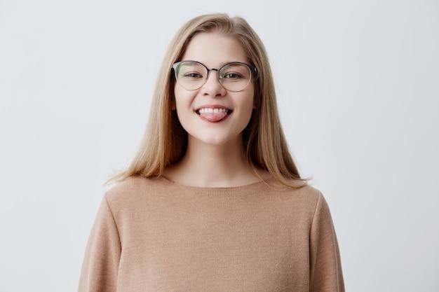Garota engraçada otimista com cabelo liso loiro, vestindo blusa marrom e óculos, mostrando a língua enquanto posava contra fundo cinza studio. emocional positivo jovem fêmea fazendo caretas