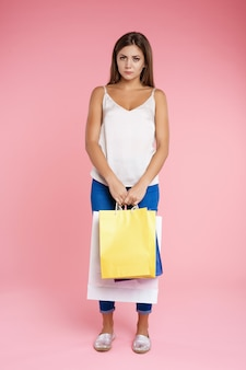 Garota engraçada parece triste segurando o monte de sacos depois das compras