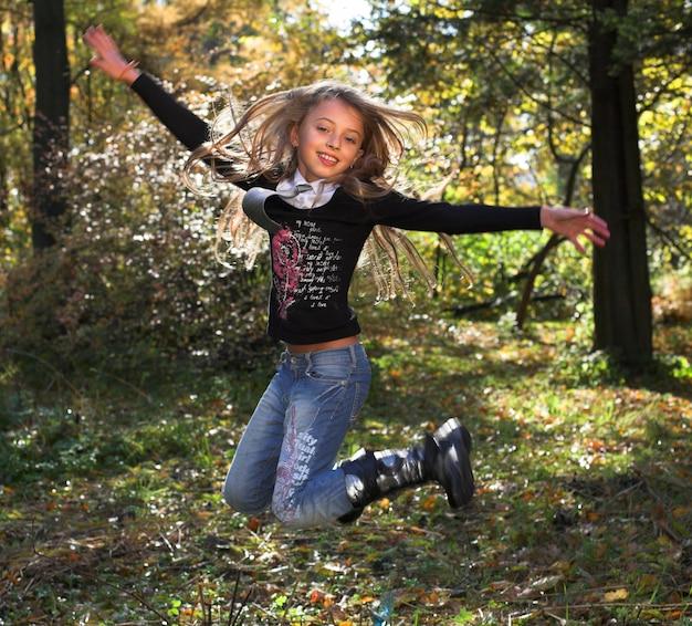 Garota engraçada pulando ao ar livre