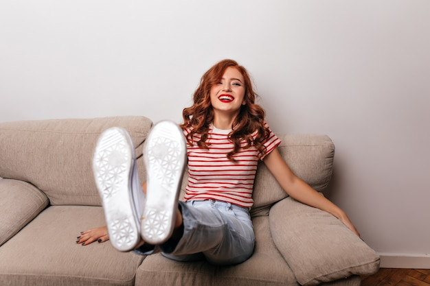 Garota engraçada relaxada sentada no sofá com um sorriso. senhora ruiva satisfeita posando no sofá e rindo.