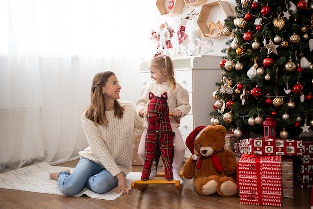 Garota engraçada se divertindo com a mãe em casa perto de árvore de natal