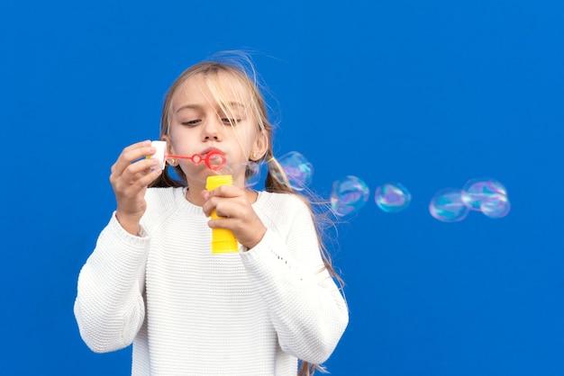Garota engraçada soprando bolhas de sabão