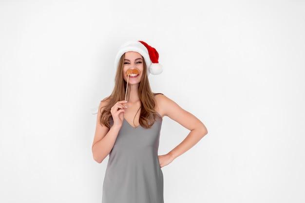 Garota engraçada usa chapéu de papai noel e finge bigode isolado no fundo branco festa de ano novo