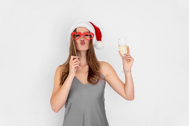 Garota engraçada usando chapéu de papai noel e óculos de mentira segurando taça de champanhe na festa de ano novo
